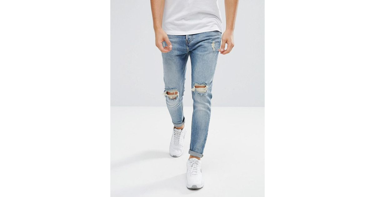 Pull&Bear Ripped Jeans In Carrot Fit In Mid Wash Blue for men