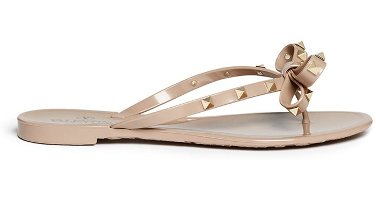 f18622f6a0c7 Lyst - Valentino  rockstud  Bow Flat Jelly Sandals in Natural
