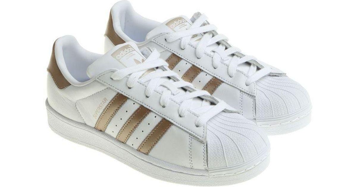 pas mal 428fe 1cc4c Adidas Originals White And Bronze Superstar W Sneakers