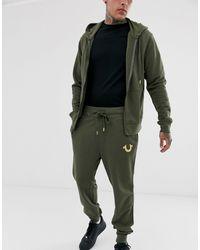 Buddah - Joggers kaki affusolati con fondo aderente e logo metallico di True Religion in Green da Uomo