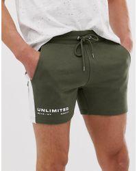 Pantalones cortos ajustados caqui de punto de estilo más corto con raya en el lateral y estampado de texto ASOS de hombre de color Green