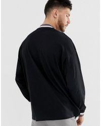 Camiseta extragrande larga de manga larga con aberturas laterales y cuello alto con ribetes ASOS de hombre de color Black