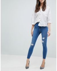 ASOS Blue Ridley High Waist Skinny Jeans In Pretty Mid Wash With Rip And Repair And Reverse Stepped Hem