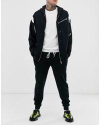 Joggers affusolati neri con elastico in vita bianco di ASOS in Black da Uomo