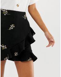 Mini-jupe portefeuille à fleurs avec volants Liquorish en coloris Black