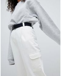ASOS Tapered Jeans With Curved Seams And Belt In Off White With Utility Side Pocket