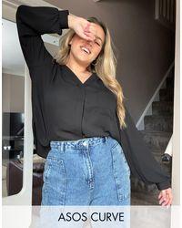 ASOS DESIGN Curve - Blusa nera a maniche lunghe con tasca di ASOS in Black