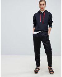 5ee908b2f7 Pantalon de jogging en satin avec bande logo femme de coloris noir