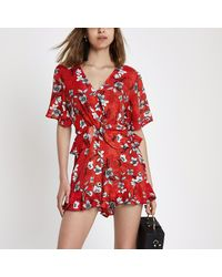 1c3ec2d3c30 River Island Red Floral Knot Front Frill Playsuit in Red - Lyst
