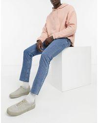 ASOS – Schmal geschnittene Stretch-Jeans mit unbehandeltem Saum - Blau