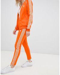 adidas Originals - Three Stripe Cigarette Trousers In Orange - Lyst