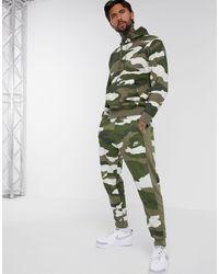 Nike – Club Essentials – Jogginghose mit Bündchen und Military-Muster - Grün