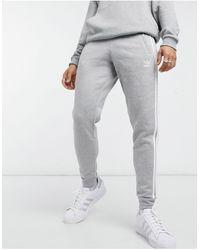 adidas Originals – adicolor – Eng geschnittene Jogginghose mit den drei Streifen - Grau