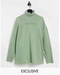 Collusion Vestido verde pálido estilo camiseta con cuello alto y logo en relieve