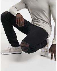 Another Influence Vaqueros pitillo negros con rodillas rasgadas