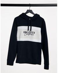 Hollister – er Kapuzenpullover mit Farbblock-Logo auf der Brust - Schwarz