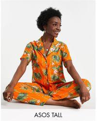ASOS ASOS DESIGN Tall – Exklusiver Pyjama aus Modal mit kurzärmligem Hemd und Hose mit Palmenmotiv - Orange