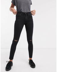 Bershka Jeans skinny push-up con strappo al ginocchio - Nero