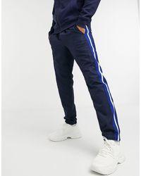 Lacoste - Joggers blu navy con riga laterale - Lyst