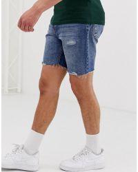 6a50650d43fd Bershka Pantaloncini di jeans slim blu medio con fondo grezzo e strappi