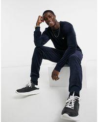 Emporio Armani – Loungewear – Set mit Sweatshirt und Jogginghose aus marineblauem Velours mit silberfarbenem Logo