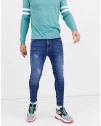 ASOS Superstrakke Jeans Met Powerstretch En Slijtplekken - Blauw