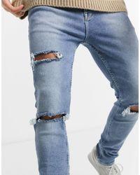 ASOS Jean skinny ultra-déchiré en stretch renforcé à délavage vintage léger - Bleu