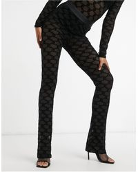 Juicy Couture – e, schmal zulaufende Hose aus aufgeflocktem Mesh mit Logo, Kombiteil - Schwarz