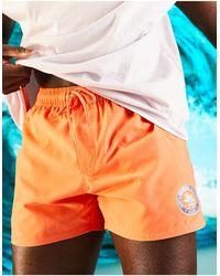 ASOS Swim Shorts With Wellness Graphic - Orange