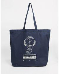 ASOS Wellness - Tote bag oversize avec imprimé - Bleu marine
