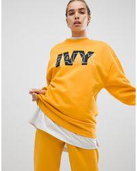 Ivy Park Sudadera con logo en amarillo