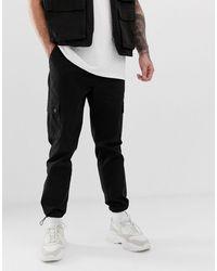 ASOS Pantalones cargo tapered en negro con muletillas