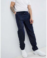 ASOS Pantalones holgados con rayas de lentejuelas en azul marino
