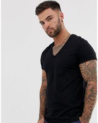 ASOS Camiseta negra con vuelta en la manga y cuello de pico pronunciado - Negro