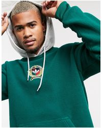 adidas Originals Sudadera polar verde con capucha con escudo universitario