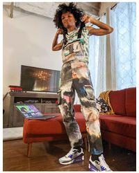 ASOS – Latzhose mit weitem Bein, Cargotaschen und Graffiti-Print - Weiß
