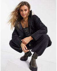 Miss Selfridge – Wattierte Kunstpelz-Jacke mit Kapuze - Schwarz