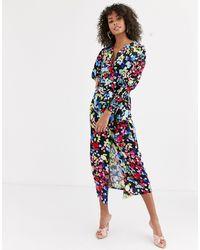 Never Fully Dressed – Vorn gewickelte Bluse mit Bindegürtel und Blumenmuster - Blau
