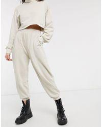 "Bershka Joggers oversize beige con slogan ""No Item"" - Neutro"