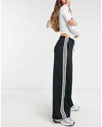 adidas Originals – adicolor – e Hose mit weitem Beinschnitt und drei Streifen - Schwarz