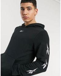 Reebok Tuta sportiva da allenamento con logo vector stampato sulla manica nera - Nero