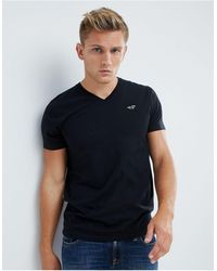 Hollister Core - T-shirt slim nera tinta unita con scollo a V e logo a gabbiano - Nero
