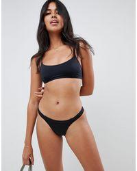 ASOS – Mix-and-Match – Tanga-Bikinihose aus recyceltem Material mit seitlichem Riemendesign - Schwarz