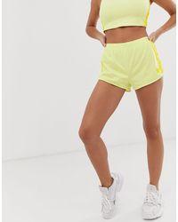 adidas Originals – adicolor – Neongelbe Shorts mit den 3-Streifen