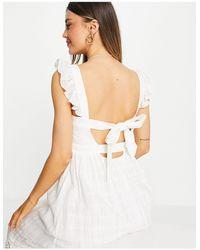 Forever New Robe mi-longue en dentelle à manches à volants et dos nu avec nœud et découpes - Blanc