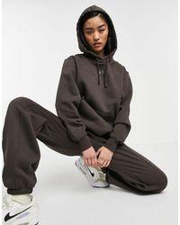 Nike - Felpa con cappuccio neutra marrone scuro con logo metallizzato - Lyst
