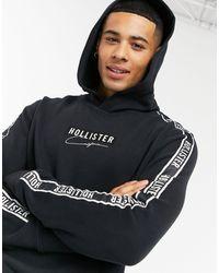 Hollister Felpa con cappuccio e nera con logo centrale e fettuccia sulle maniche - Nero