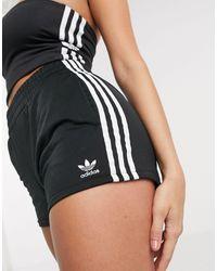 adidas Originals – adicolor – e Shorts mit hohem Bund und drei Streifen - Schwarz