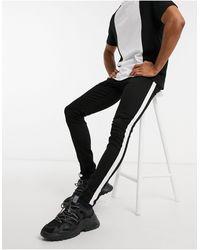 Criminal Damage – Enge Jeans mit seitlichem Zierband - Schwarz