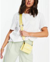 Claudia Canova Bolso amarillo con tira para el hombro y solapa con logo